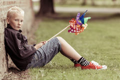 Sad blond boy sits against wall holding whirligig Royalty Free Stock Images