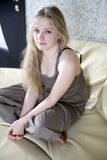 Sad blond lonely teen girl sitting on sofa Royalty Free Stock Images