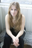 Sad blond teen girl sitting on balcony Stock Photos