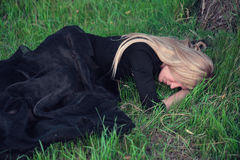 Sad blond woman. In black dress lying on the grass Royalty Free Stock Photo