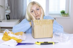 Sad blond woman sitting by the table after unboxing a parcel, all objects on the table are in mess royalty free stock images