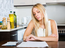 Sad blonde girl reading document Royalty Free Stock Photography