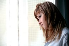 Sad blonde beside window Stock Images