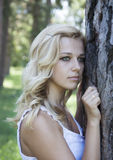 Sad blonde woman. Beautiful sad woman near the tree Royalty Free Stock Photo