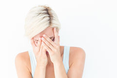 Sad blonde woman crying with head on hands. On white background Stock Photography