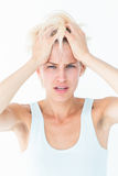 Sad blonde woman with head pain holding her head Royalty Free Stock Photos