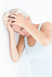 Sad blonde woman with head pain holding her head Royalty Free Stock Image