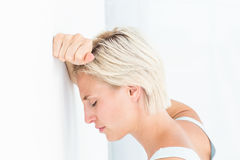 Sad blonde woman with her head on wall. On white background Royalty Free Stock Photography
