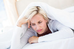Sad blonde woman lying on the bed Royalty Free Stock Photography