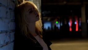 Sad blonde woman standing alone outside nightclub, melancholy, loneliness. Stock photo stock photo