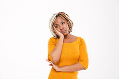 Sad bored african american young woman in yellow dress standing Royalty Free Stock Photography