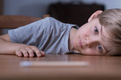 Sad bored boy. Portrait of sad bored boy laying his head on table Royalty Free Stock Photography