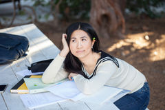 Sad and bored girl student lying in a pile of books. In a picturesque park Royalty Free Stock Photography