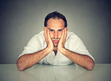 Sad bored man sitting at table in his office. Sad bored young man sitting at table in his office royalty free stock photography