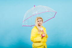 Sad bored woman wearing raincoat holding umbrella. Sad bored blonde woman wearing yellow raincoat holding transparent umbrella waiting for rain Royalty Free Stock Photography