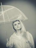 Sad bored woman wearing raincoat holding umbrella. Sad bored blonde woman wearing yellow raincoat holding transparent umbrella waiting for rain. Black and white Royalty Free Stock Photo