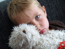 Sad boy. Sad child with teddybear on black sofa Royalty Free Stock Images