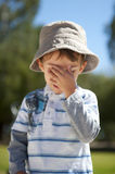 Sad Boy. Sad young boy shows emotions and covers his eyes with one hand royalty free stock photos
