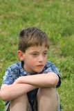 Sad boy. Boy sitting, staring away very serious Stock Photography