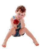 Sad boy with Apple in hand. Sad little boy in denim short shorts sitting on the floor with bare feet and sad looking at a big red juicy Apple , the boy does not Stock Photo