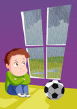 Sad boy for bad  weather. Sad boy looking out through window on the rain as they couldn't play  football outside Stock Photography