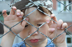 Sad boy behind bars Stock Image