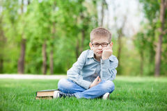 Sad boy with book on green grass Stock Image