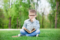 Sad boy with book on green grass Royalty Free Stock Photos