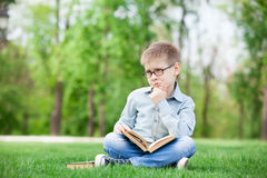 Sad boy with book on green grass Stock Photo