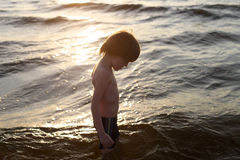 Sad boy with bowed head on the background of the sea at sunset. Boy looking down profile standing in the sea royalty free stock photography