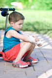 Sad boy with broken arm sits on scooter Royalty Free Stock Images