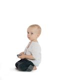 Sad boy with a cellphone. A sad boy with a cellphone sitting on his knees Royalty Free Stock Photography