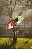 Sad boy with colorful rainbow umbrella Stock Images