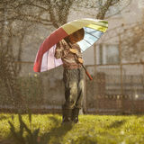 Sad boy with colorful rainbow umbrella Royalty Free Stock Photography