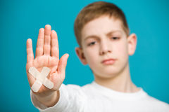 Sad boy with cross white adhesive plaster on his hand Royalty Free Stock Image
