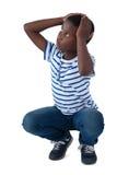 Sad boy crouching with hand on head Stock Image