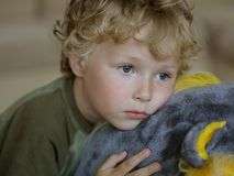 Sad boy. Sad curly boy lay on toy Royalty Free Stock Images
