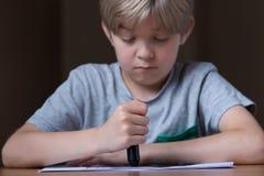 Sad boy doing a drawing Stock Photo