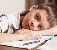 Sad boy doing homework Stock Images
