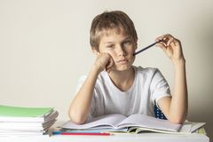 Sad tired boy doing homework. Education, school, learning difficulties concept. Sad boy doing homework. Education, learning difficulties concept stock images