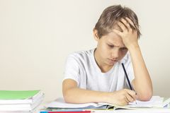 Sad boy doing homework. Education, school, learning difficulties concept. Sad boy doing homework. Kid education, school, learning difficulties concept royalty free stock images