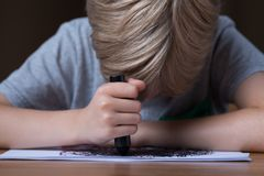 Sad boy doodling. Close up of sad boy doodling with black crayon Royalty Free Stock Images
