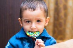 Sad boy eating Lollipop Stock Photography