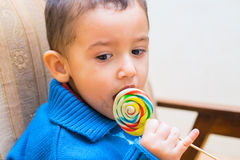 Sad boy eating Lollipop. Sad boy eating a candy on a stick Royalty Free Stock Photo