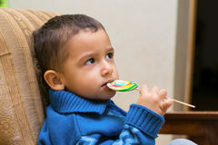 Sad boy eating Lollipop Royalty Free Stock Photos