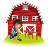 A sad boy in front of the barnhouse Stock Photography
