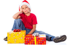 Sad boy with gift box in christmas hat Stock Image