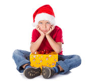 Sad boy with gift box in christmas hat. Sitting on the floor, isolated on white Stock Photo