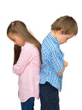Sad boy and girl - ajar, in quarrel, on white. Sad kids at odds with each other, after argument or quarrel, look down - shot isolated on white background stock photography