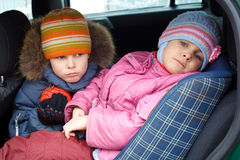 Sad boy with girl, in winter clothes in car. Royalty Free Stock Image